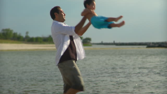 ms pan father spinning son (2-3) around in the air on beach, eastville, virginia, usa - människoarm bildbanksvideor och videomaterial från bakom kulisserna