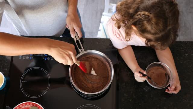 娘がチョコレートパウダーを注いでいる間、父親は鍋をかき混ぜる - dia点の映像素材/bロール