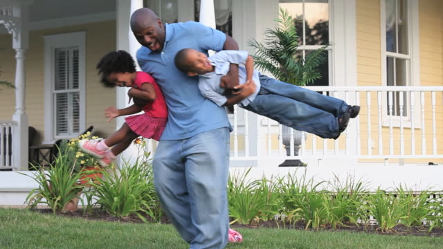 ws father swinging his two children around in front yard of home / richmond, virginia - sollevare video stock e b–roll