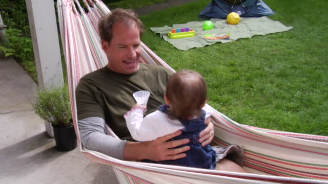 ms father swinging in hammock with baby daughter/ vancouver, bc - kelly mason videos stock videos & royalty-free footage