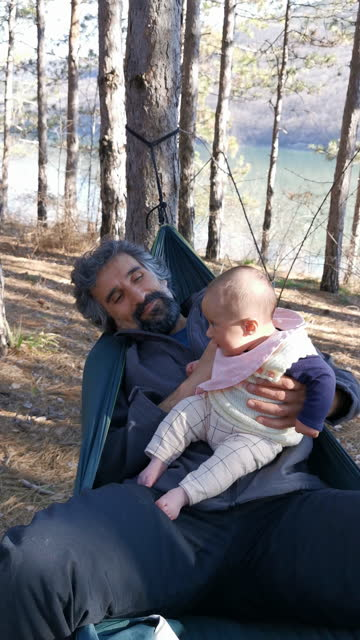 father swinging with his newborn baby in a hammock, playing and laughing together while being in the nature. spending time outdoors in the fresh air of a pine woodland during covid-19 pandemic. father's day. - pine woodland stock videos & royalty-free footage