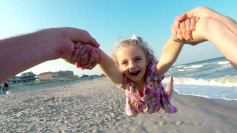 father swings daughter around as waves break on sunny beach - vacations stock videos & royalty-free footage
