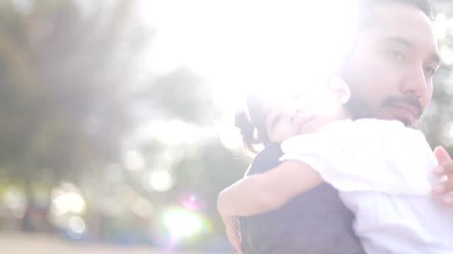 父は彼の娘の寝かし付け - 運ぶ点の映像素材/bロール
