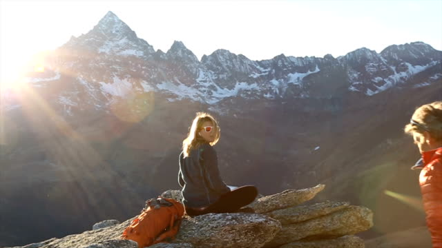Father takes picture of young girl perched above mountain valley