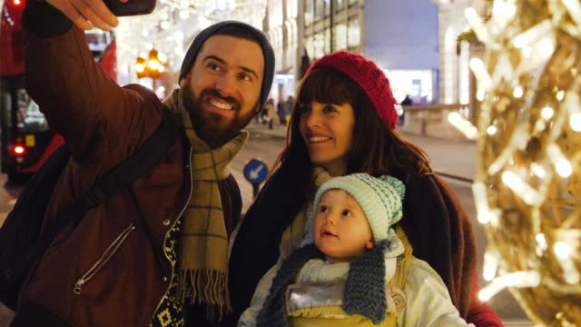 Father takes Selfie of himself and mother and child on street with christmas lights.