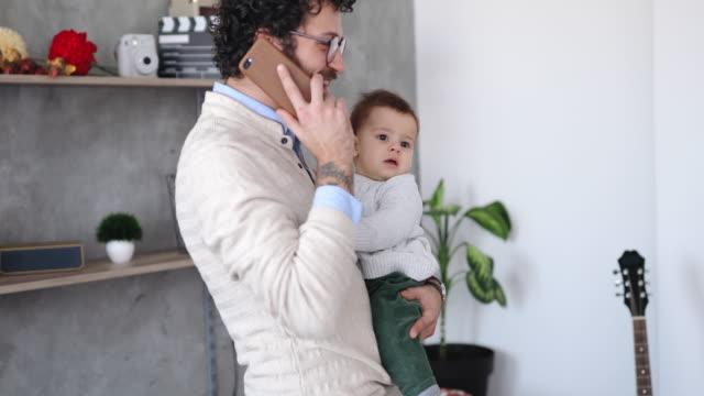 vater die pflege von baby und mit telefon - single father stock-videos und b-roll-filmmaterial