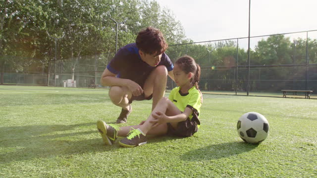 vídeos de stock e filmes b-roll de father taking care of his injured daughter on soccer field,4k - família com um filho