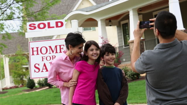 stockvideo's en b-roll-footage met ms ds father taking family photo in front of new home with sold sign / richmond, virginia, usa - voor