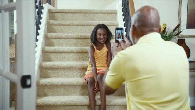 MS Father taking picture of daughter (8-9) sitting on stairs with mobile phone camera / Bothell, Washington State, USA
