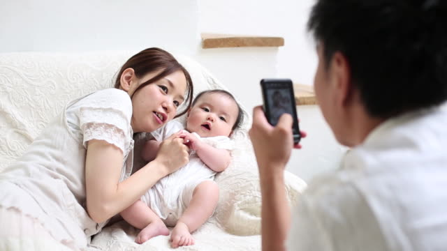 father taking pictures of his wife and baby girl with smartphone - 両親点の映像素材/bロール