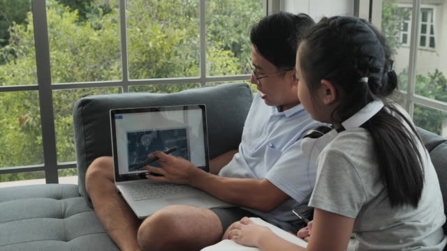 father teaches daughter books by using laptop - genderblend stock videos & royalty-free footage