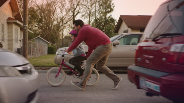 vídeos de stock, filmes e b-roll de ws slo mo. father teaches daughter how to ride bicycle on neighborhood street. - showing