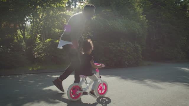 vídeos de stock, filmes e b-roll de father teaches daughter to ride her bike - família monoparental