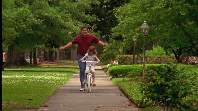 a father teaches his daughter to ride a bicycle. - gehweg stock-videos und b-roll-filmmaterial