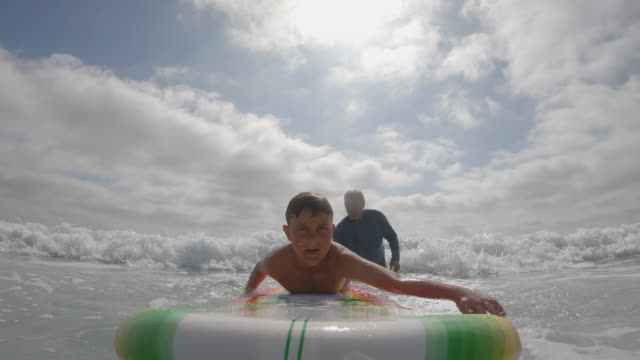 A father teaches his son boy child learning how to surf surfing. - Slow Motion