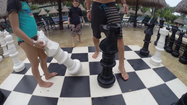 Father teaches son and daughter how to play chess on a giant board at a resort.