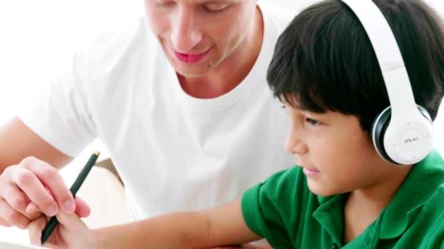 vídeos y material grabado en eventos de stock de padre enseña a su hijo a estudiar en línea - intergénero
