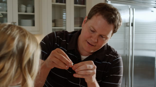 father teaching a daughter to thread something - see other clips from this shoot 1420 stock videos and b-roll footage