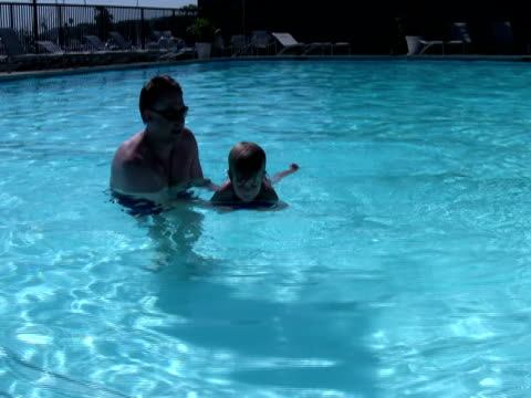 stockvideo's en b-roll-footage met father teaching child to swim; floating on kick-board - genderblend