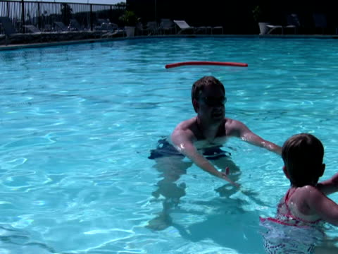 stockvideo's en b-roll-footage met father teaching child to swim; swimming from pool edge - buitenbad