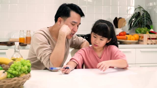 vidéos et rushes de père enseignant fille fait ses devoirs dans la cuisine moderne - genderblend