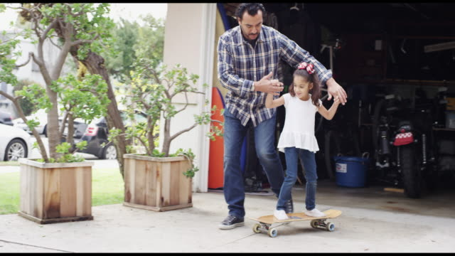 vídeos de stock, filmes e b-roll de father teaching daughter how to skateboard - entrada para carros