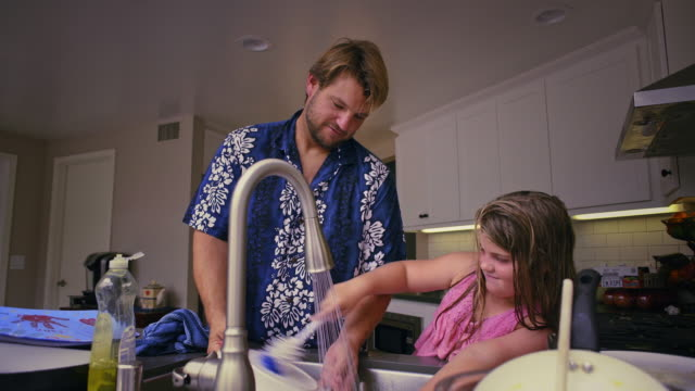 Father teaching daughter to clean dishes. Med.