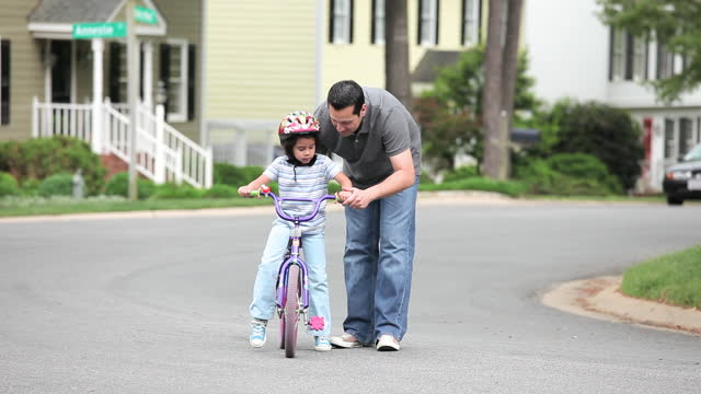 father teaching daughter to ride bicycle in suburban neighborhood - sports helmet stock videos and b-roll footage