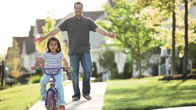 father teaching daughter to ride bicycle on sidewalk in neighborhood - single father stock videos & royalty-free footage