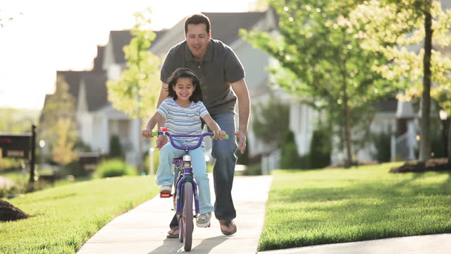 vídeos de stock, filmes e b-roll de father teaching daughter to ride bicycle on sidewalk in neighborhood - passageiro