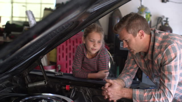 ms father teaching his daughter about cars. - daughter stock-videos und b-roll-filmmaterial