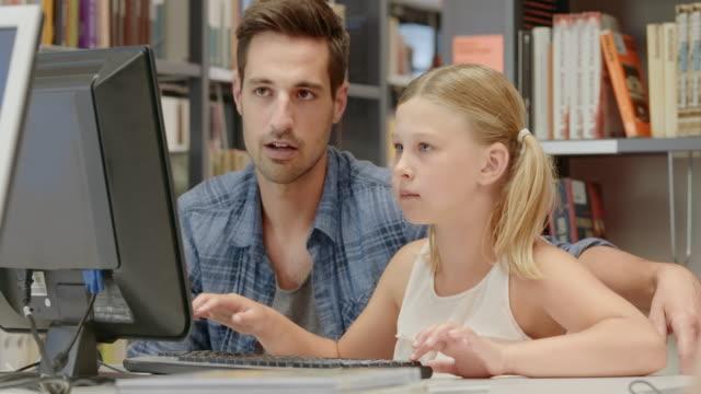 vídeos y material grabado en eventos de stock de ds padre e hija de enseñanza de exploración biblioteca de libros en la computadora - teclado de ordenador