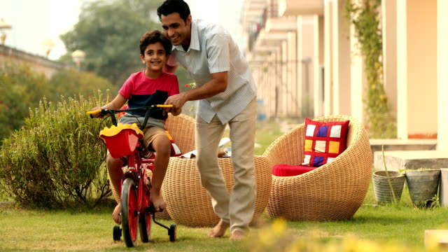 MS Father teaching his son to ride bicycle in lawn / Sonipat, Haryana, India