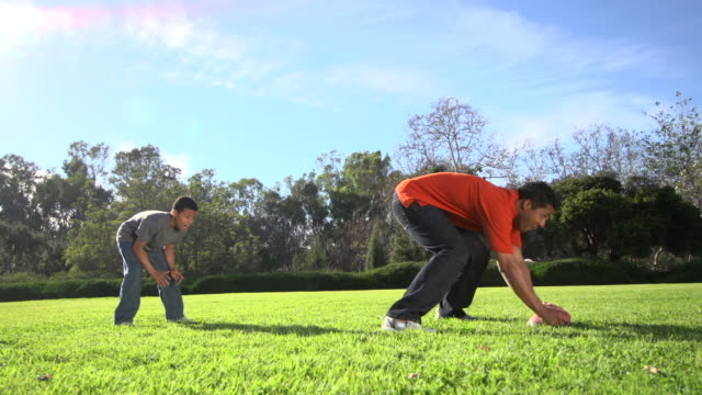 a father teaching his sons how to play american football.  - slow motion - inarcare la schiena video stock e b–roll