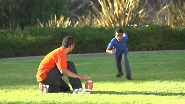 a father teaching his sons how to play american football.  - kicking stock videos & royalty-free footage