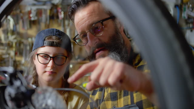 slo mo father teaching his teenage daughter how to service the chain on her bike - repairing stock videos & royalty-free footage
