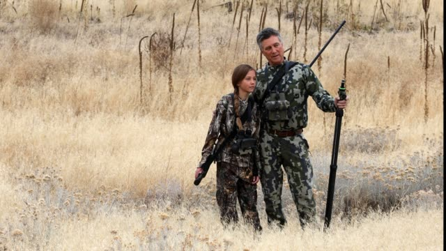 father teaching hunting to daughter while standing on field in forest - idaho stock videos & royalty-free footage