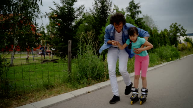 father teaching little daughter to roller skate - genderblend stock videos & royalty-free footage