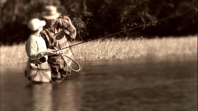 MS PAN SELECTIVE FOCUS Father teaching son (12-13) fly fishing in river, sepia toned / Tampa, Florida, USA