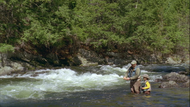 vidéos et rushes de ws father teaching son (8-9) fly fishing on grand lake stream / maine, usa - maine