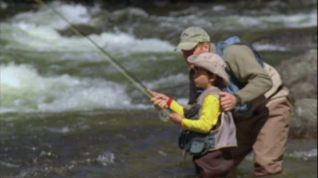 MS FOCUS Father teaching son (8-9) fly fishing on Grand Lake Stream / Maine, USA