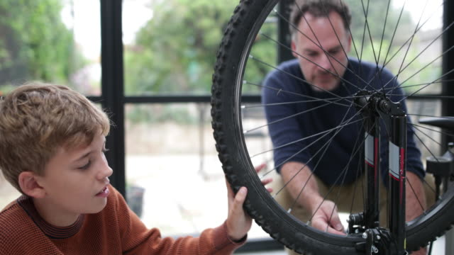 vídeos de stock e filmes b-roll de father teaching son how to care for his bicycle - família monoparental