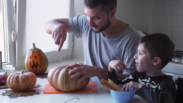 Father teaching son how to carve halloween pumpkin
