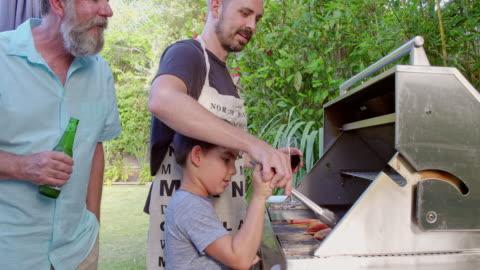 vídeos y material grabado en eventos de stock de padre hijo enseña a cocinar en la barbacoa - asado alimento cocinado