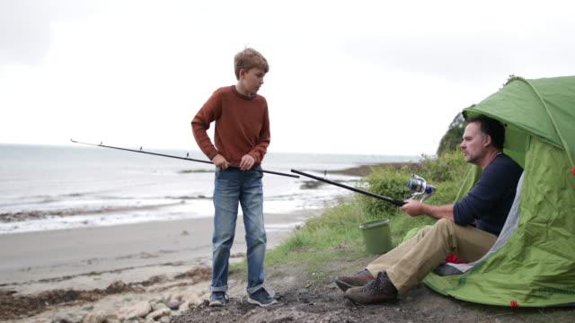 vídeos y material grabado en eventos de stock de father teaching son how to fish - caña de pescar