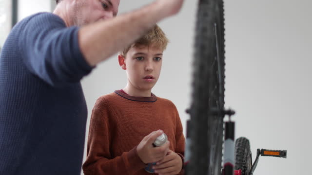 vidéos et rushes de father teaching son how to fit new brakes on a bike - famille monoparentale