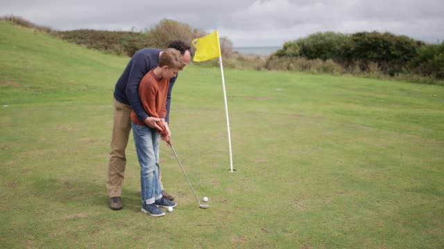 Father teaching son how to play golf
