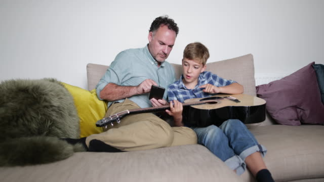 Father teaching son how to play guitar using a smartphone