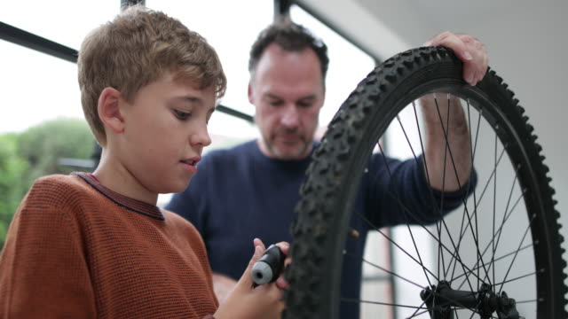 stockvideo's en b-roll-footage met father teaching son how to pump bike tyres - behendigheid