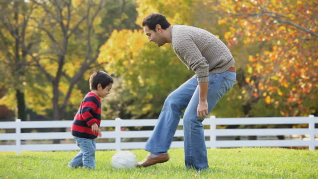 WS PAN Father teaching son (2-3) kicking soccer ball in back yard / Richmond, Virginia, USA
